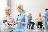 Nurse Measuring Blood Pressure Of Elderly Woman At Retirement Home. Assisting Senior People poster