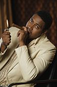 foto of risque  - Portrait of African man lighting cigar - JPG