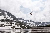 Helicopter Over Mountain Lake. Wooden Hut In Mountains And Red Helicopter poster