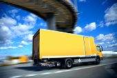 stock photo of delivery-truck  - speed yellow delivery truck on road or highway - JPG