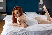 Young Redheaded Woman Half-naked Lying On The Bed. Lazy Morning Weekend At Home. poster