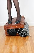 image of stocking-foot  - Woman in high heel shoes standing on leather suitcase overfilled with fashion clothing - JPG