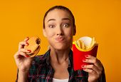 Hungry Girl Eating Burger And French-fries On Yellow Background. Cheat Meal And Junk Food. Studio Sh poster
