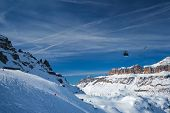 View of a ski resort piste with people skiing in Dolomites in Italy with cable car ski lift. Ski are poster
