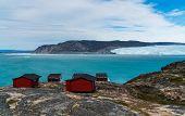 Greenland glacier nature landscape with famous Eqi glacier and lodge cabins. Tourist destination Eqi poster