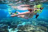 foto of under sea  - Young woman snorkeling over coral reef in tropical sea with clear transparent water - JPG