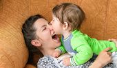 Baby Bites Moms Nose. Happy Mother With Baby. A Boy Bites His Mothers Nose On The Couch. Having Fun  poster