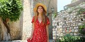 Summer Holiday In Italy. Portrait Of Young Woman With Straw Hat And Red Dress Walking In Sicilian Vi poster