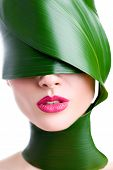 A close up portrait of a beautiful girl with a head wrapped up in a leave posing in the studio over  poster