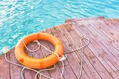 Orange Lifebuoy With Rope On A Wooden Pier Near Sea. Yellow Ladder And An Orange Lifebuoy With Rope  poster