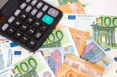 Taxes And Spending Concept. Tax Word Writen On Wooden Cubes. Euro Banknotes Laid Out In A Semicicirc poster