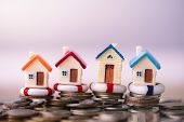 Home Insurance. House Model In Lifebuoys On Coins Stack. Securing Large Value Of Home By Applying An poster