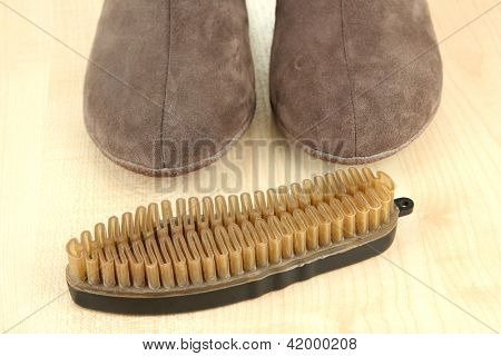 Brush for suede shoes, on wooden background