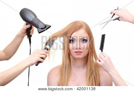Beautiful woman and hands with brushes, scissors and hairdryer isolated on white
