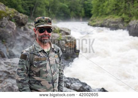 Smiling middle aged Hiker in a mountain river. Russia. Primorskiy kray.