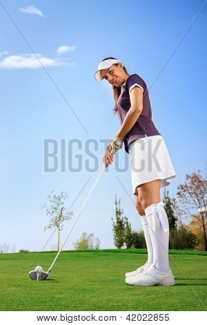 Golf woman player green putting hole golf ball