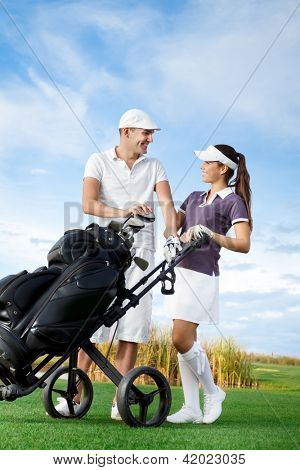 Couple playing golf on a sunny day looking at each other and laughing