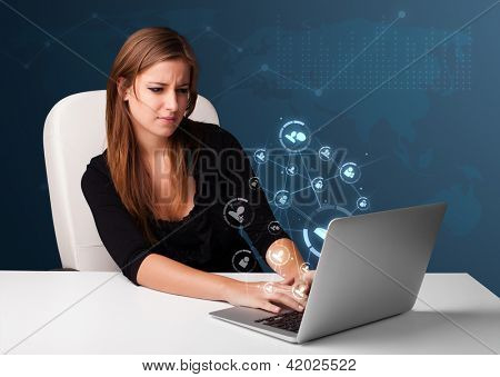 Beautiful young lady sitting at desk and typing on laptop with social network icons comming out