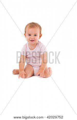 Happy Babymädchen sitzen zwischen den Fersen auf den Boden, lächelnd.