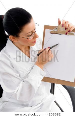Side View Of Female Doctor Indicating Writing Pad On White Background