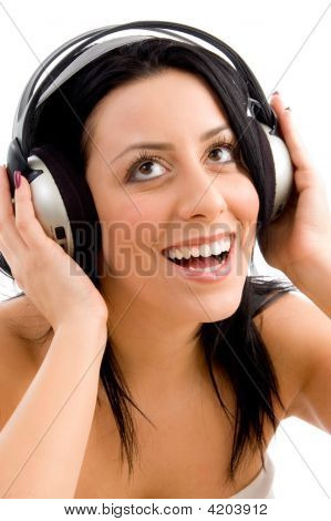 Front View Of Smiling Female Enjoying Music Against White Background