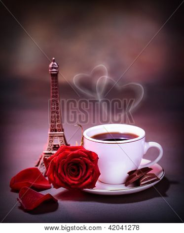 Picture of white cup with coffee and chocolate decorated with red rose on the table in Paris, romantic honeymoon, celebration anniversary in France, Valentine day holiday, love and romance concept