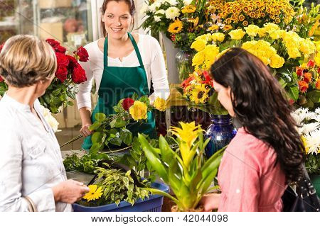 Florist woman preparing bouquet customers flower shop market happy
