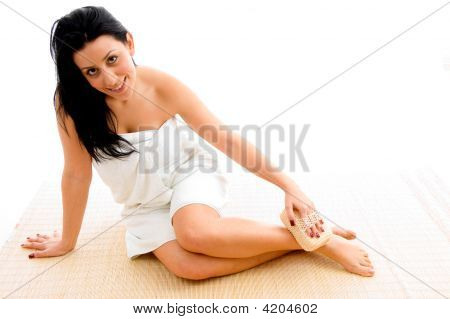 Front View Of Woman Scrubbing Her Leg On An Isolated Background
