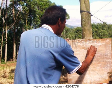 rural teacher witing on a Blackboard