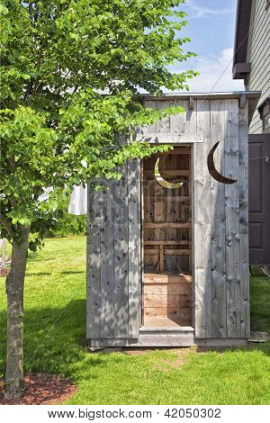 A wooden outhouse ideally located in the backyard.
