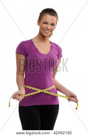 Young Woman holding a measure tape around her waist isolated on a white background