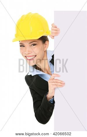 Engineer entrepreneur architect business woman showing blank white sign for copy space. Young multiracial Caucasian / Asian Chinese young professional wearing suit and hard hat.
