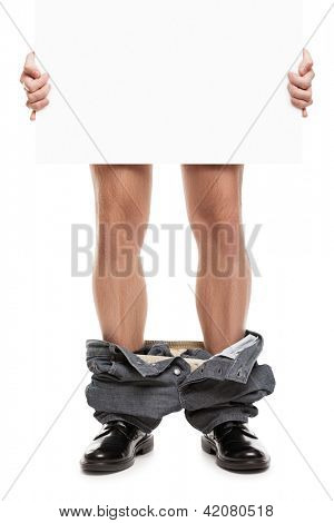 Caught with pants down - man in black shoes and jeans dropped down holding in hands blank placard