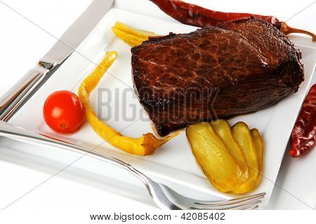 meat chunk served on white with knive and fork