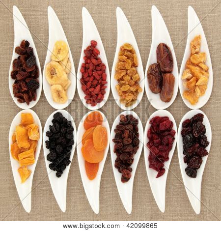 Dried fruit selection in porcelain dishes over beige linen background.