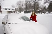 picture of scrape  - A pretty woman scraping snow off her car during a snowstorm - JPG