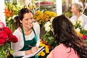image of flower shop  - Happy florist writing flower shop talking customer woman - JPG