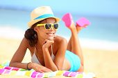 stock photo of lie  - Beach woman funky happy and colorful wearing sunglasses and beach hat having summer fun during travel holidays vacation - JPG