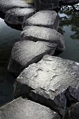 stock photo of stepping stones  - Stone path across a tranquil pond in a Japanese garden - JPG