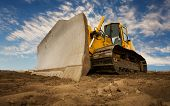 stock photo of bulldozer  - A large yellow bulldozer at a construction site low angle view - JPG