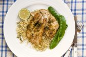 Grilled fish fillets with cous cous and snow peas.  Garnished with dill, capers and lime.