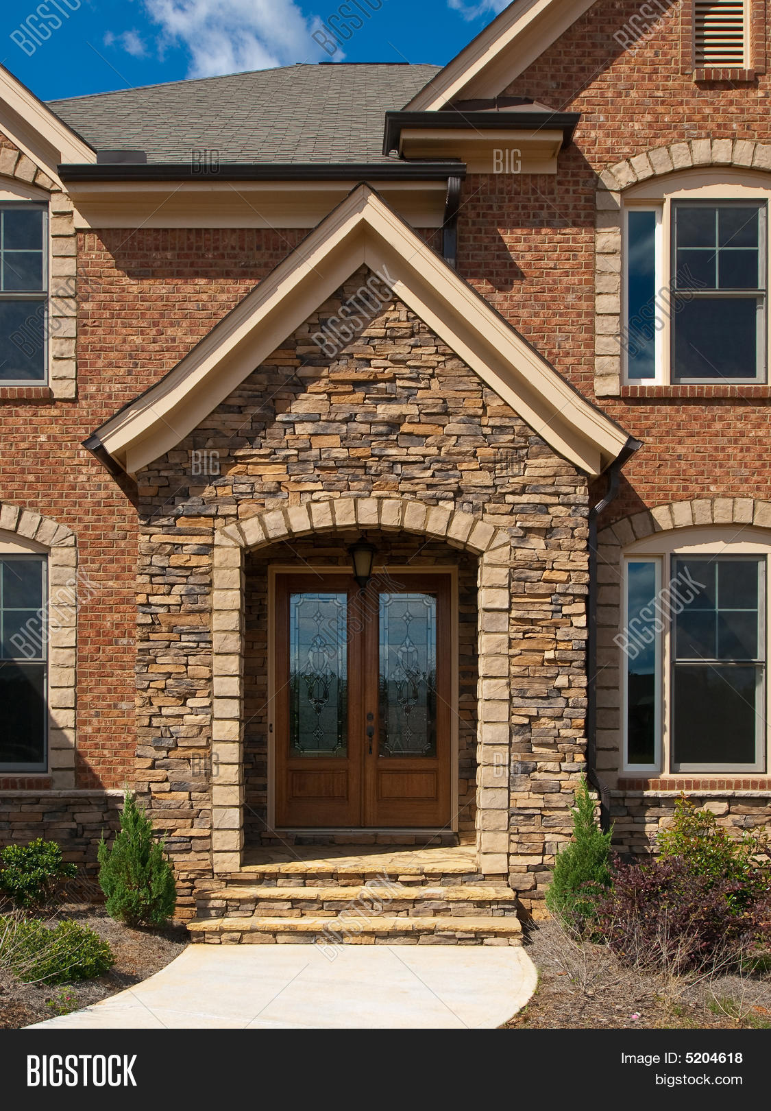 luxury model home exterior stone arch front entrance - Luxury Stone Exterior