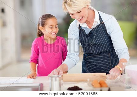 loving grandma baking cookies for granddaughter at home