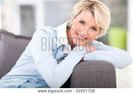 pretty senior woman relaxing on a couch at home