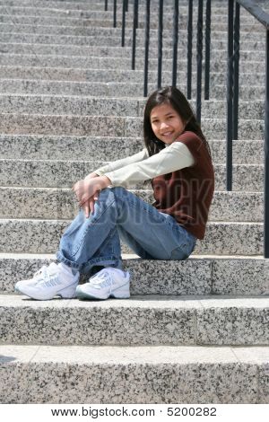 Young Girl Sitting On Large Granite Stairs