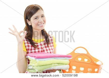The woman is holding a Laundry basket