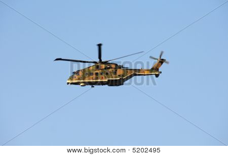 Military Helicopter In Action On Blue Sky