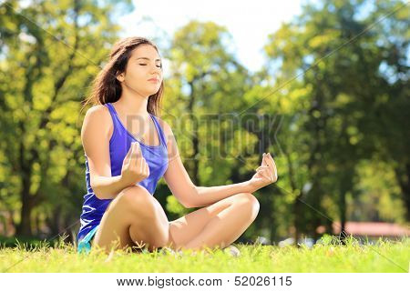Young female athlete in sportswear meditating seated on a grass in a park
