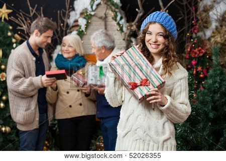 Portrait of beautiful young woman holding Christmas present with family standing in background at store