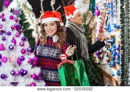 Portrait of happy young woman carrying shopping bag with man looking at decorations in store